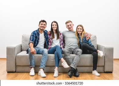 The four happy friends sit on the sofa on a white wall background
