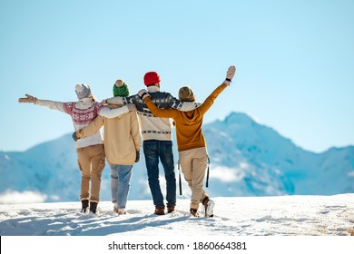 Four happy friends are standing and embracing against snow capped mountains at sunny day. Winter vacations concept