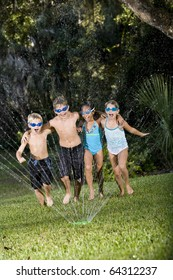 Four happy kids running arm in arm shouting and laughing, soaked by lawn sprinkler, ages 7 to 9 years