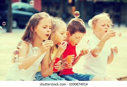 Four happy kids in school age sitting together and blowing soap bubbles