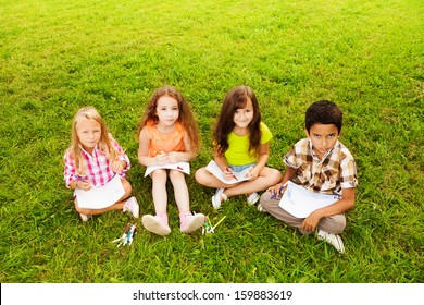 Four happy kids, three girls and boy sitting together on the lawn and drawing pictures