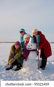 Four happy ladies with snowman at the wintry field