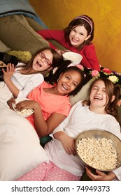 Four happy little girls on a couch eat popcorn