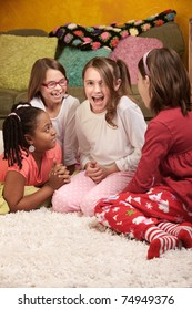Four happy little girls sharing stories at a sleepover
