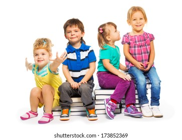 Four happy little kids sitting on the stairs of books
