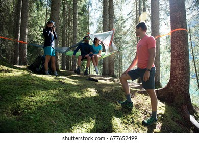Four happy man and woman hanging tent camping in forest woods during sunny day near lake.Group of friends people summer adventure journey in mountain nature outdoors.Travel exploring Alps,Dolomites