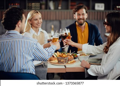 Four happy muliethnic freinds dressed smart casual cheering with alcohol while sitting at restaurant.
