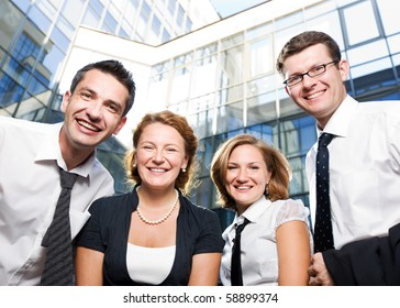 Four happy office business workers staying in front of business building. Beautiful people of different ages showing unity in their team outdoors.