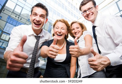 Four happy office workers staying in front of office building and showing thumb-ups. Professional workers smiling and laughing for the camera outdoors.