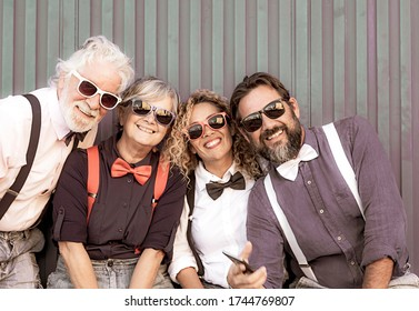Four happy people enjoying party and fun. Two generations family, large smiles, bow ties and suspenders, blue background