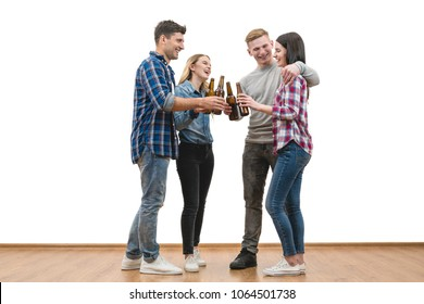 The four happy people hold bottles of beer on a white wall background