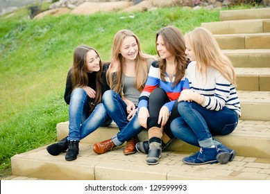 Four happy smiling teenage girls women female friends outdoors sitting on stairs