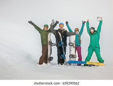 Four happy and smiling young friends snowboarders with their hands up in the mountains at Krasnaya Polyana in the fog and poor visibility