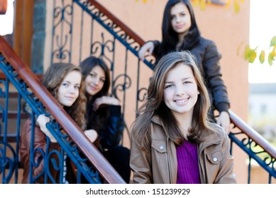 Four happy teen girls friends outdoors smiling and having fun