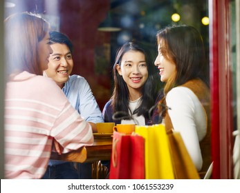 four happy young asian adults male and female relaxing chatting talking in coffee shop after shopping, shot through window glass.
