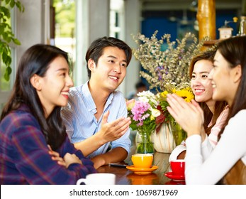 four happy young asian adults men and women chatting talking in coffee shop.