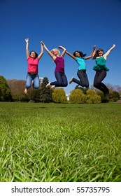 Four happy young women jumping into the air