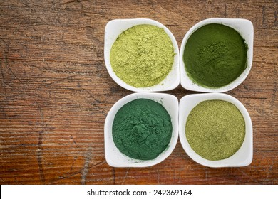 four healthy green dietary supplement powders (spirulina, chlorella, wheatgrass and moringa leaf) in white bowls on a grunge wood