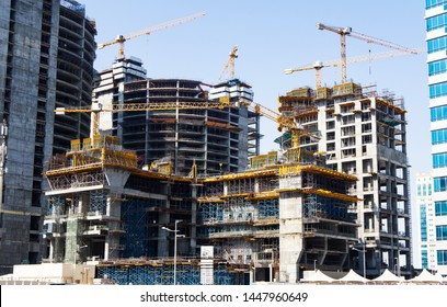 Four high-rise buildings under construction. Big construction site with cranes and scaffolding