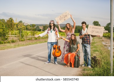 Four hippies standing and hitchhiking on the road with placards
