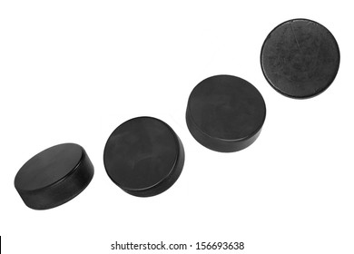 Four hockey pucks, lined up in a row on a white background
