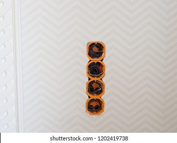 four holes in the wall with electrical wires to connect sockets