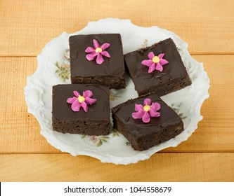 Four homemade chocolate brownie squares with chocolate frosting and pink and yellow piped flowers on a white flowered plate against a wood table.