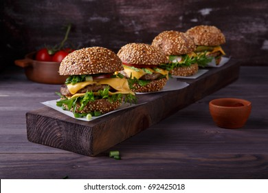 Four homemade hamburgers on wooden table. Buns with sesame seeds, beef burgers and various ingredients. Rustic style.