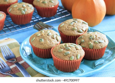 Four homemade pumpkin muffins garnished with fresh pepitas sitting on blue pumpkin plate with fresh pumpkins in background