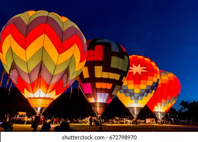 Four hot air balloons preparing to rise in the early morning dawn