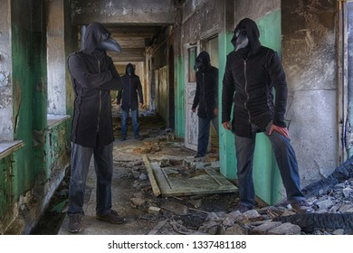 Four identical  mans in plague doctor masks, in hood and with a knife in an abandoned hospital or an insane asylum. Maybe picture for horror movie