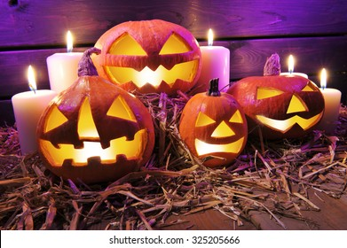 four illuminated halloween pumpkins on straw in front of old weathered wooden board in crazy violet halloween light