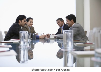 Four Indian business people discussing at conference table