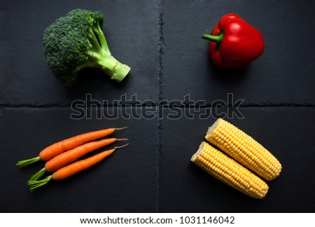 Four individual vegetables; broccoli, pepper, carrots, corn on the cob on slate plate. Organic produce.