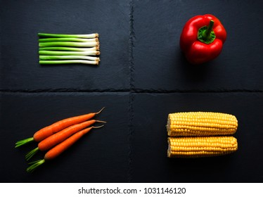 Four individual vegetables; onions, pepper, carrots, corn on the cob on slate plate