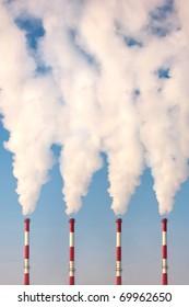 four industrial chimneys polluting
