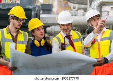 Four Industry Engineers standing in the Boiler room of factory ,having discussion on the drawing paper planing for new construction extension design concept.