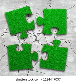 Four jigsaw puzzles of green grass texture, on cracked light grey concrete floor background, high angle view.