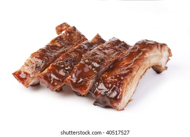 Four juicy barbecued pork ribs on a white background.