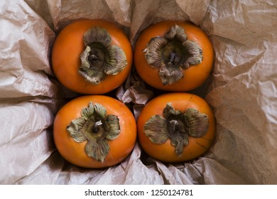 Four kaki fruits (persimmon) in a box with paper background. Top view