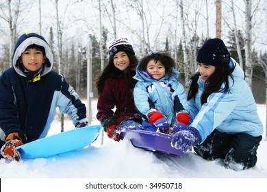 Four kids enjoying winter outdoors sledding
