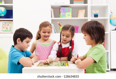 Four kids playing board game in their room