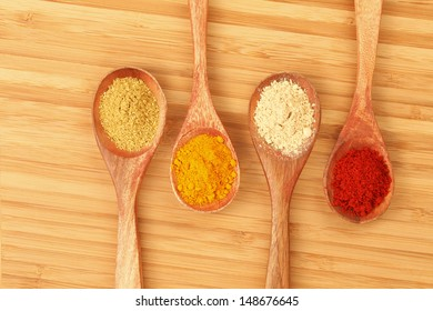 Four kind of Spices in Wooden Spoons (on wooden chopping board).