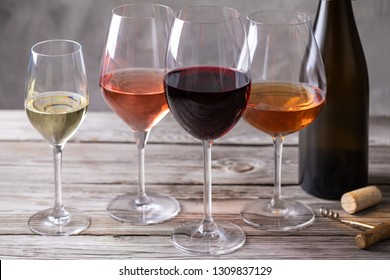 Four kinds of wine in wineglasses near the bottle on old wooden table. Pink, orange, white and red wine