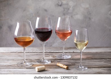 Four kinds of wine in wineglasses on old wooden table. Pink, orange, white and red wine