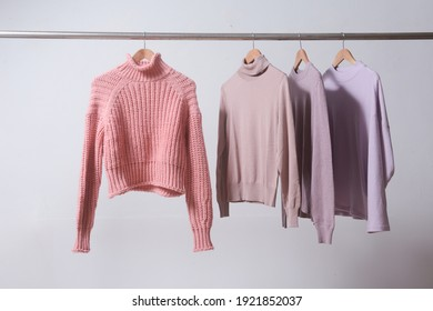Four knitted, turtleneck sweaters hang on hangers. Bright sweaters