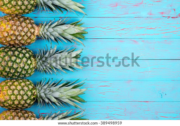 Quattro grandi ananas maturi ordinatamente disposti in fila con spazio copia su sfondo in legno a tema tropicale