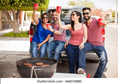 Four Latin friends laughing and having fun while grilling burgers at a barbecue and drinking some beer
