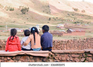 Four latin kids sitting on the wall and admiring a beauty of the nature.