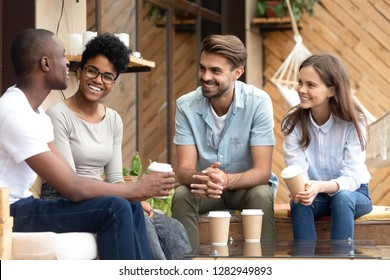 Four laughing diverse people positive multi-ethnic friends sitting in cozy cafe summer terrace drink coffee telling funny stories from life feels happy and satisfied enjoy time together on weekend